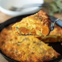 A slice of frittata on a spatula showing the sweet potato and sage inside
