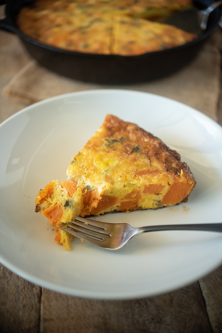 A white plate and a fork eating a slice of frittata
