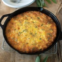 Sweet potato and sage frittata in a cast iron skillet with fresh sage