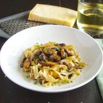 A large white bowl of tagliatelle with mushrooms with a glass of wine and Parmesan cheese