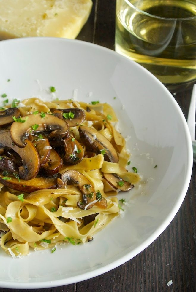 A closeup of the meaty mushrooms on top of fresh tagliatelle