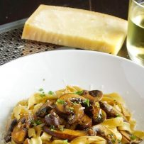 A white bowl full of tagliatelle with mushrooms