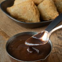 Serving a spoonful of tamarind date paste with samosa in the background