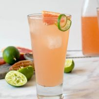 A side view of tequila Paloma cocktail with a lovely pink grapefruit color
