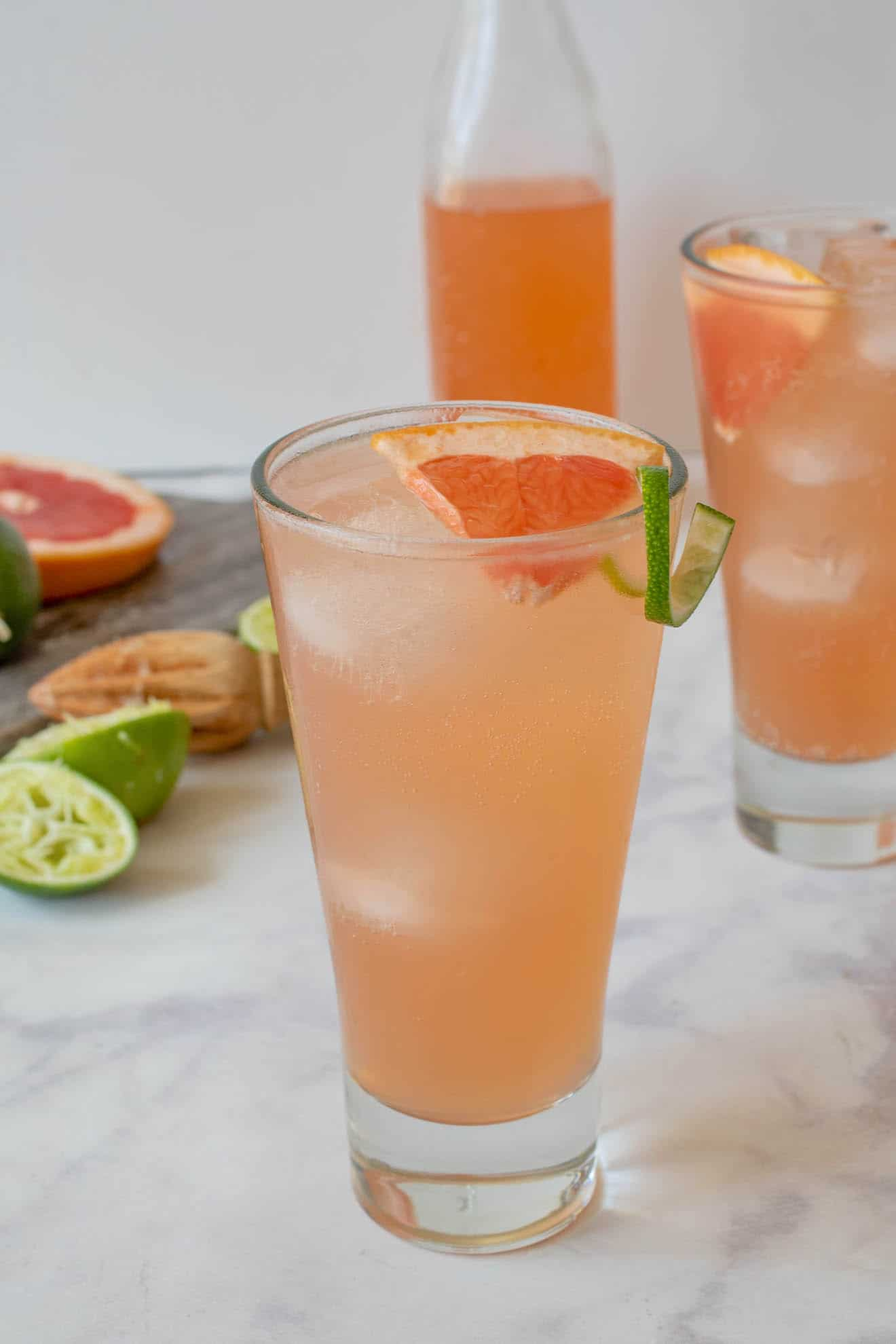 A tall glass of tequila Paloma garnished with a wedge of fresh grapefruit and lime rind