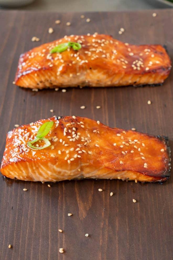 2 freshly cooked teriyaki salmon filets on a board