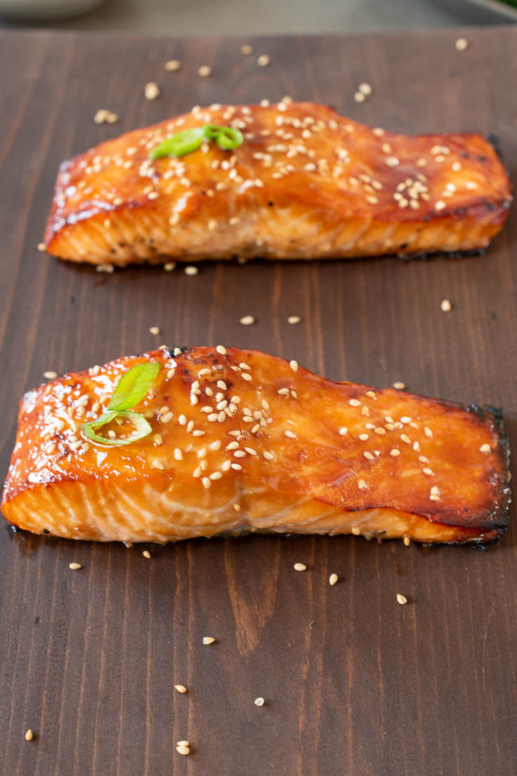 2 salmon filets on a board garnished with sesame seeds