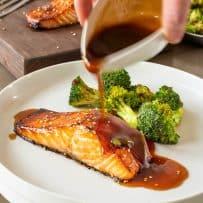 Pouring teriyaki sauce over cooked salmon