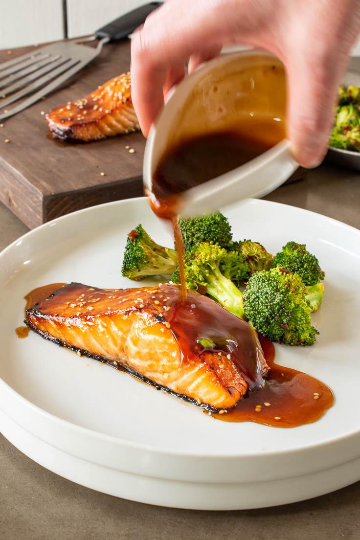 Pouring teriyaki sauce over salmon on a white plate with broccoli
