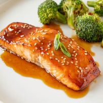 Teriyaki Glazed Salmon on a white plate with green onion and broccoli