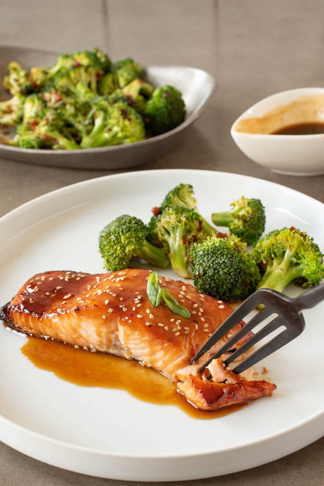 Using a fork to get a bite of teriyaki glazed salmon on a white plate with broccoli