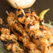 Teriyaki chicken skewers piled up and ready to be eaten, sprinkled with black sesame seeds