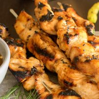 Teriyaki chicken skewers lined up on a serving platter garnished with greens and a side of sauce