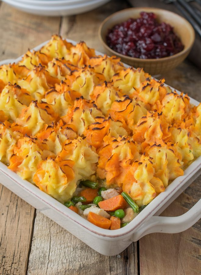 Orange and yellow mash topping leftover turkey and vegetables in a casserole dish with cranberry sauce