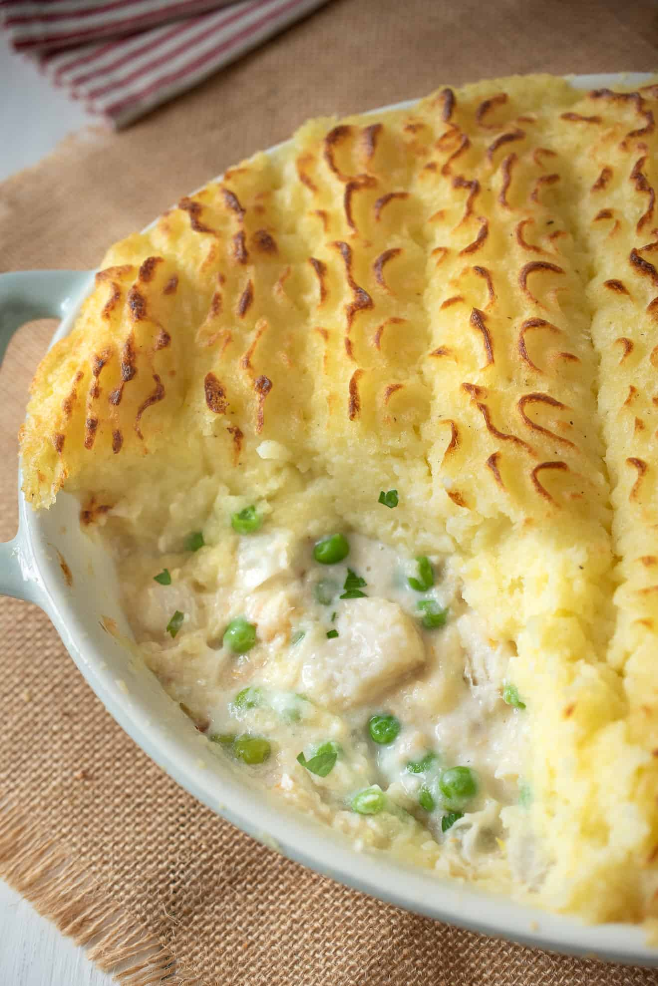 A closeup of the filling of British fish pie showing the green peas