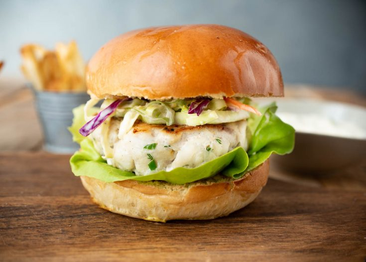 A tilapia burger in a bun with lettuce and coleslaw