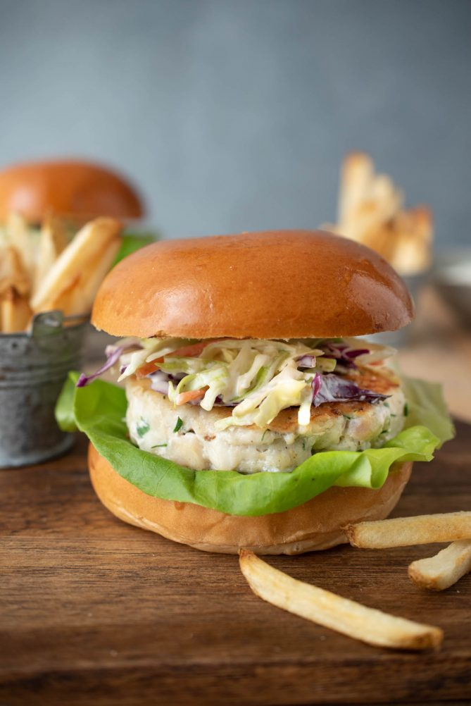 A side view of a tilapia burger on a bun with French fries