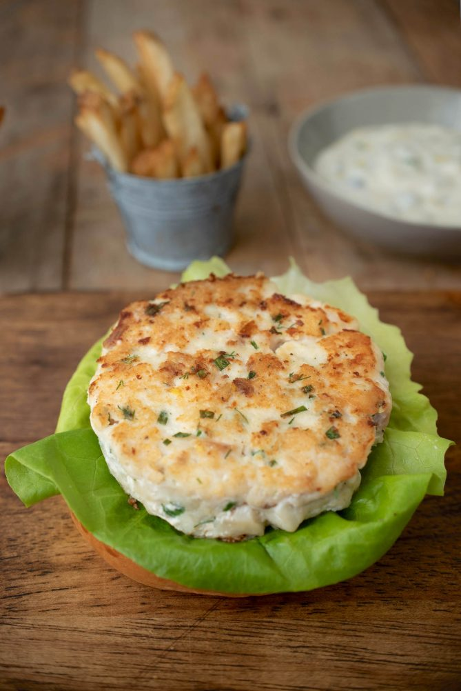 A tilapia burger patty on a bed of lettuce and a bottom bun