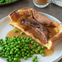 1 toad in the hole sausage inside batter on a white plate with peas and onion gravy