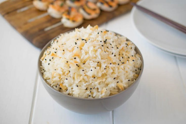 Toasted coconut rice in a grey bowl garnished with black sesame seeds