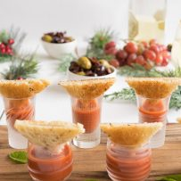 Different small glasses of tomato soup with triangles of grilled cheese sandwiches balanced on top on a serving board
