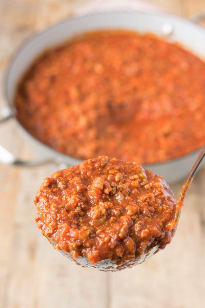 A ladle full of Bolognese sauce