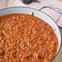 A large pan of Bolognese sauce with a ladle