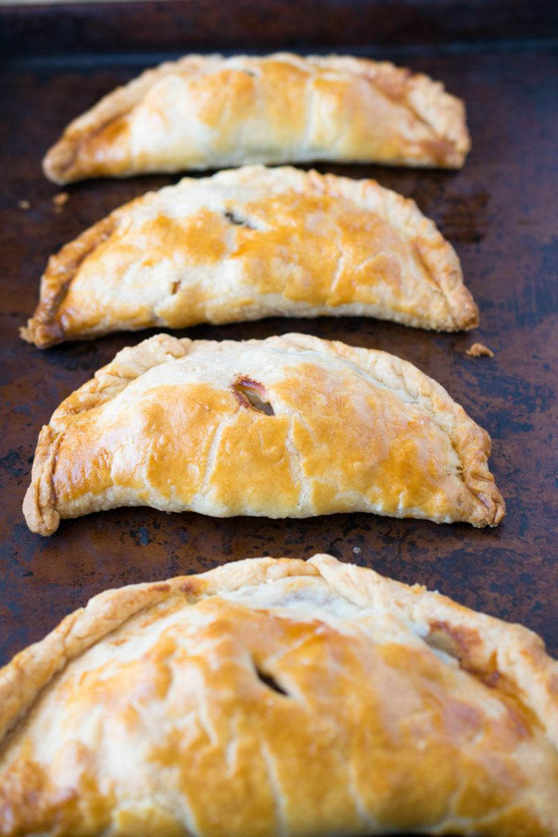 4 Traditional Cornish pasties lined up on a baking sheet