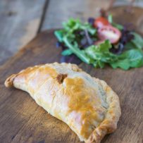 A Cornish Pasty on a serving board with a salad of greens