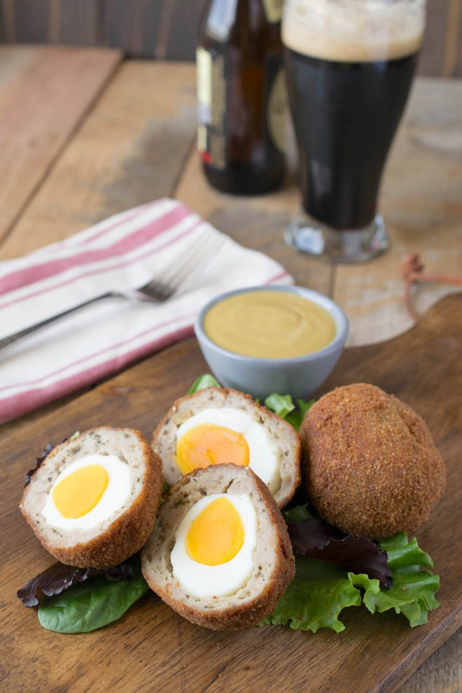 Scotch eggs cut in half showing the yellow yolk and sausage inside