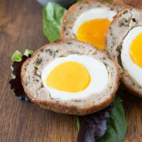 A closeup of the inside of a Scotch egg showing the bright yolk