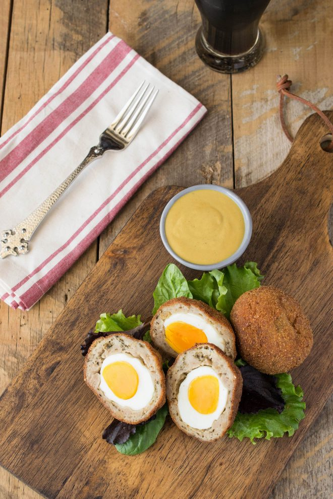 Scotch eggs viewed from overhead served with mustard sauce