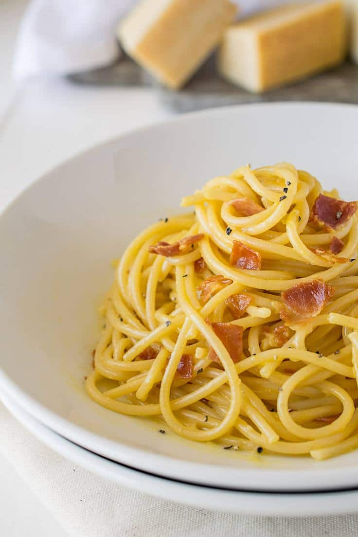 A closeup of Traditional Spaghetti Carbonara in a white bowl showing the creaminess and pancetta pieces