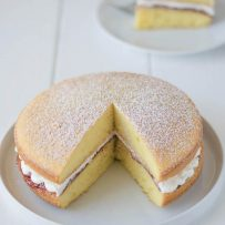 A whole Victoria Sponge Cake with a piece removed