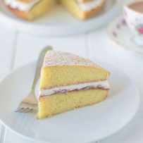 A slice of sponge cake sandwiched with cream and jam on a plate with a fork