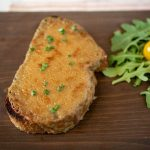 A slice of traditional Welsh rarebit on a wooden board with a tomato salad