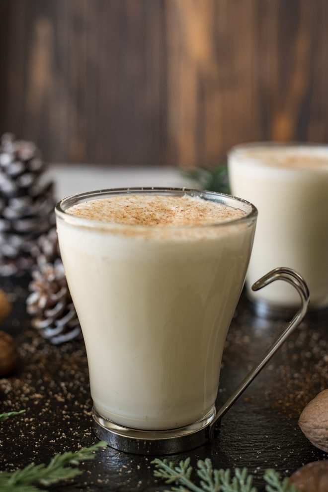 Eggnog in a glass mug with a foamy topping and grated nutmeg