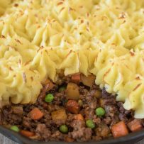 A closeup of the ground beef filling with carrots and peas