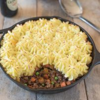 Shepherds pie with ground lamb, carrots and peas topped with piped mashed potato