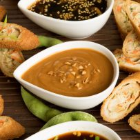 Savory and sweet Asian sauces surrounded by spring rolls