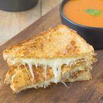 A triple grilled cheese sliced in half showing the melted cheese inside on a serving board with tomato basil soup