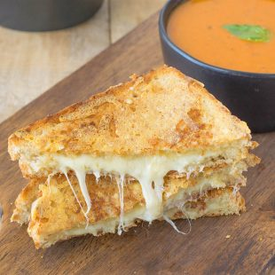 Atriple grilled cheese sliced in half showing the melted cheese inside on a serving board with tomato basil soup