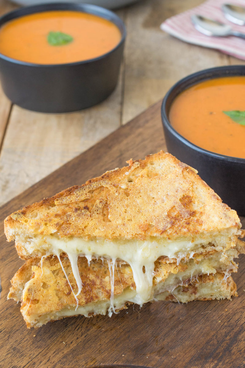 Grilled cheese cut in half with cheese oozing out on a board with a bowl of tomato soup