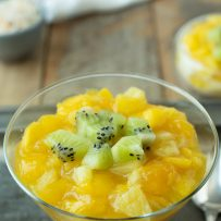 Bright orange and yellow mango and pineapple in a glass with rice pudding with chopped kiwi