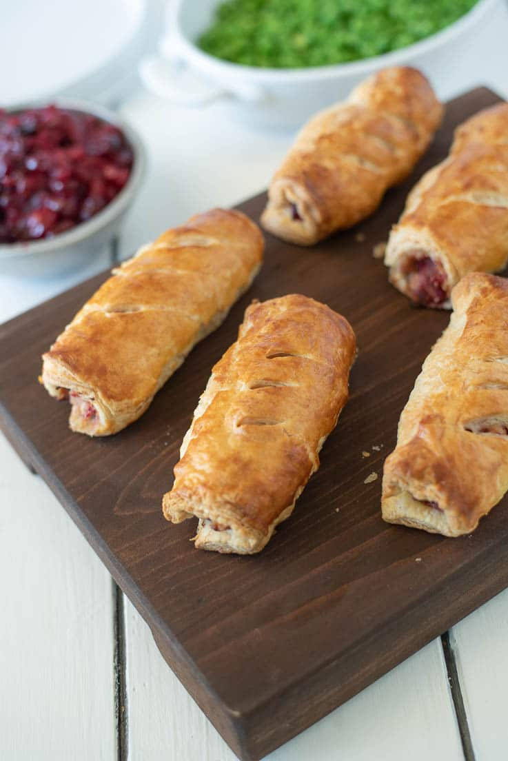 Turkey, stuffing and cranberry sausage rolls are served on a board with a side of cranberry sauce and peas