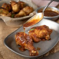 Pouring Spicy Chili Sauce over Turmeric Spiced Fried Chicken