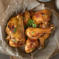 Drumsticks and thighs of Turmeric Spiced Fried Chicken garnished with cilantro