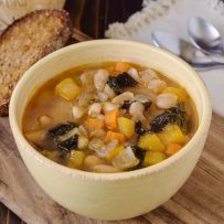 An off white bowl filled with Tuscan bean soup with bread, Parmesan and spoons