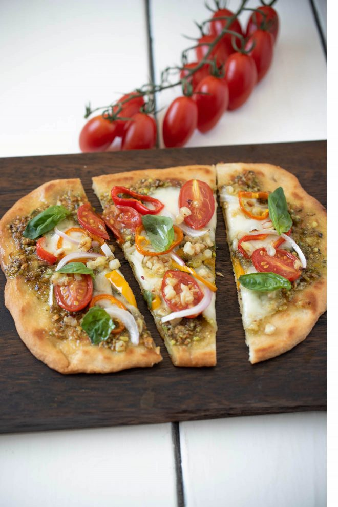 Vegetale pesto flatbread pizza cut into 3 slices on a board with cherry tomatoes on the vine