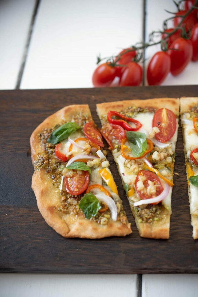 A closeup of a slice of vegetable pesto flatbread pizza showing the cherry tomatoes, red onion, corn, peppers, pesto and fresh basil